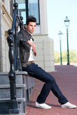 Male fashion model in leather jacket sitting outdoors — Stock Photo
