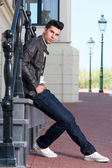 Attractive young man in black leather jacket sitting outdoors — Stock Photo