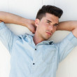 Male fashion model with arms raised behind head — Stock Photo
