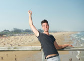 Happy young man with arm raised at the seaside — Stock Photo