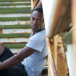 Handsome african american man sitting on stairs outdoors — Stock Photo #29458331