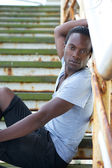 Male fashion model sitting on steps outdoors — Stock Photo