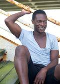 Sonriente a hombre afroamericano sentado en pasos al aire libre — Foto de Stock