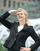 Business woman standing with hand salute outdoors — Stock Photo
