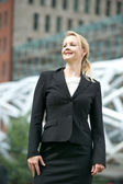 Businesswoman smiling outdoors in the city — Stock Photo
