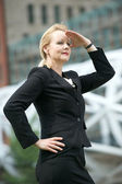 Businesswoman with hand to head salute in the city — Stock Photo