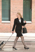Business woman walking with travel luggage in the city — Stock Photo