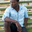 African american male fashion model sitting on stairs — Stock Photo