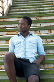 Attractive black man sitting on stairs outdoors — Stock Photo