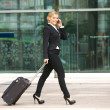 Young business woman walking and talking on phone in the city — Stock Photo