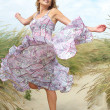 Woman with dancing with summer dress at the beach — Stock Photo