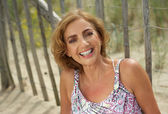 Attractive middle aged woman smiling outdoors — Stock Photo