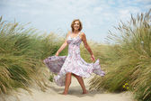 Woman dancing in the sand at the beach — Stock Photo