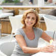 Woman smiling at restaurant with glass of water  — Stock Photo