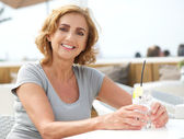 Mature woman smiling with glass of water at restaurant — Stock fotografie