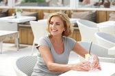 женщина, сидящая на открытом воздухе с стакан воды — Стоковое фото