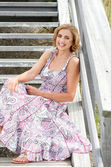 Happy woman sitting on stairs outdoors — Stockfoto