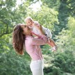 Portrait of a happy mother playing with baby in the park — Stock Photo