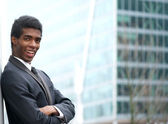Cheerful young businessman smiling in the city — Stock Photo