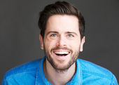 Casual young man laughing on gray background — Stock Photo