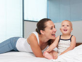 Beautiful mother laughing with cute baby in bed — Stock Photo
