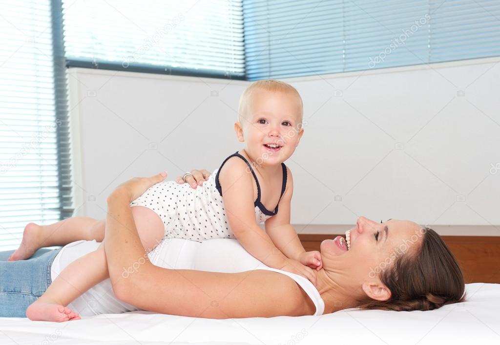 快乐妈妈环抱的可爱的宝宝躺在床上