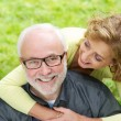 Happy older man with beautiful woman smiling outdoors — Stock Photo #32187595