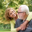Happy older couple smiling and looking at each other outdoors — Stock Photo #32187657