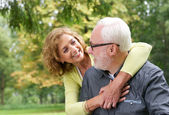 Happy older couple smiling and looking at each other outdoors — Stock Photo