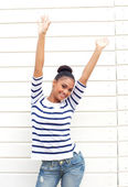 Happy young woman smiling with arms raised — Stock Photo