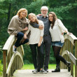 Stock Photo: Happy family standing together on a bridge in the forest