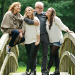 Beautiful happy family standing together in a bridge in the woods — Stock Photo
