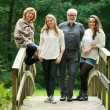 Happy family with mother father and daughters standing on bridge in the forest — Stock Photo
