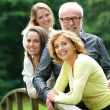 Happy mother and father standing with two daughters outdoors — Stock Photo