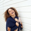 Happy young woman laughing outdoors and holding sweater — Stock Photo #32667535
