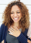Portrait of a beautiful young woman with curly hair laughing — Stock Photo