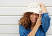 Attractive young woman smiling and wearing hat on white background — Stock Photo