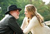 Uomo maturo con giovane donna sorridente a vicenda — Foto Stock