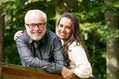 Happy mature man smiling with young woman — Stock Photo