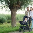 Mother and father walking outdoors and pushing baby in pram — Stock Photo