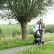 Portrait of a happy family walking outdoors with baby — Stock Photo #32908647