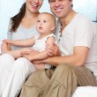 Happy loving couple holding cute baby at home — Stock Photo