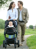 Happy mother and father smiling and pushing baby pram with child — Stock Photo