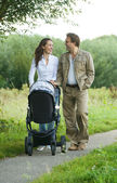 Happy mother and father pushing baby pram outdoors — Stock Photo