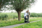 Portrait of a happy family walking outdoors with baby — Stock Photo