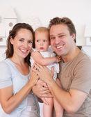 Bambino carino holding di famiglia felice a casa — Foto Stock