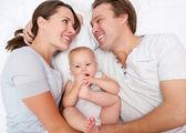 Ritratto di una donna felice e l'uomo sorridente con la cute del bambino — Foto Stock