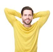 Portret van een jonge man die lacht met handen in het haar — Stockfoto