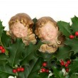 Angel figurines with green holly leaves and red berries — Stock Photo #33288701