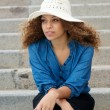 Young woman wearing white hat sitting alone outdoors — Stock Photo